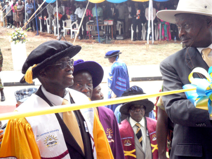 File Photo: President Museveni cuts the tape to symbolize St. Lawrence University official opening as Prof Mukiibi looks on.