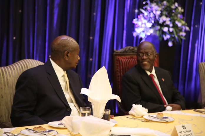 File photo: president Magufuli in a chat with President Museveni at a dinner