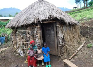 Rwanda family outside small hut