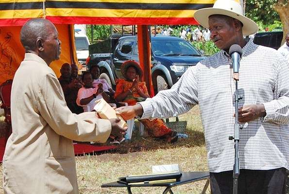President Museveni hands an envelope with money